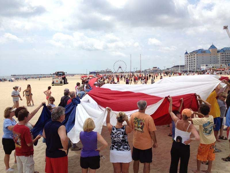 people on beach with american flag