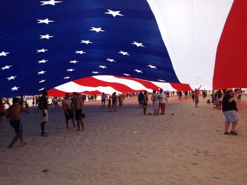 people standing under a giant american flag